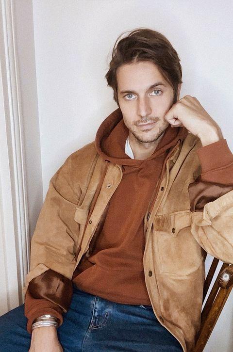Лукас Браво сидит в толстовке с капюшоном цвета ржавчины, коричневой замшевой куртке и джинсах, подперев левую руку на спинке деревянного стула