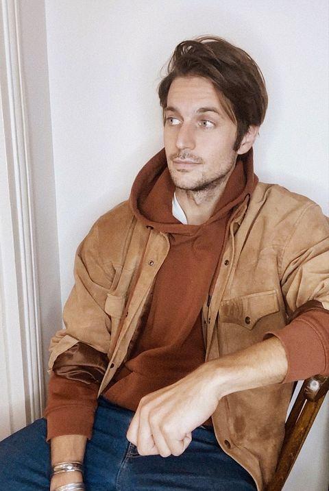 Лукас Браво сидит на деревянном стуле в толстовке с капюшоном цвета ржавчины, коричневой замшевой куртке и джинсах, смотрит направо