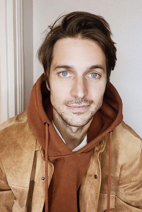 Лукас Браво в толстовке с капюшоном цвета ржавчины и коричневой замшевой куртке ухмыляется в камеру