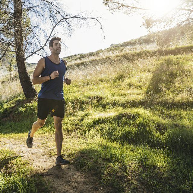 jonge man loopt hard over bospad op zomerdag