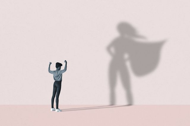 young woman flexing muscles in front of large superhero shadow on pink background