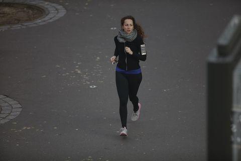 una mujer corre sola al anochecer por las calles de parís