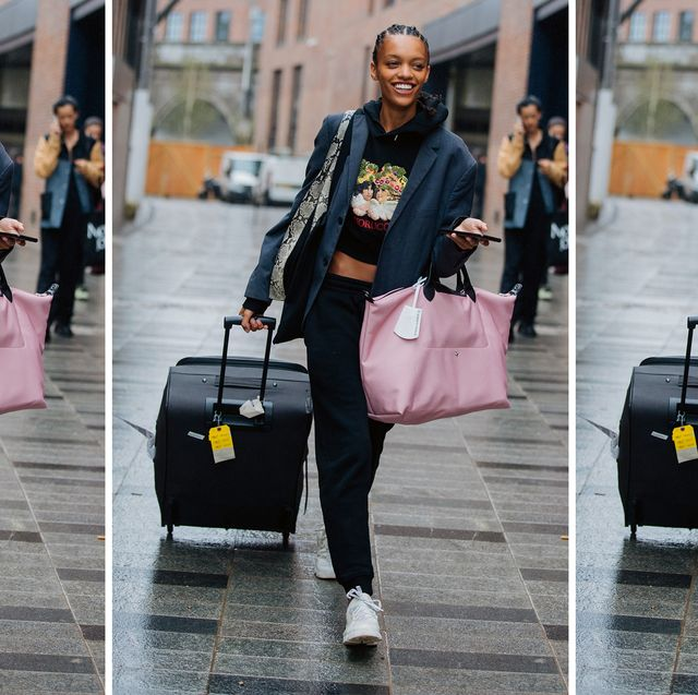 a model carries two suitcases to illustrate the best luggage on amazon for 2021