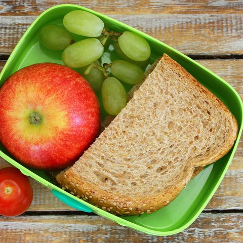 Lunch box consisting of wholegrain sandwich, fruit and cherry tomatoes