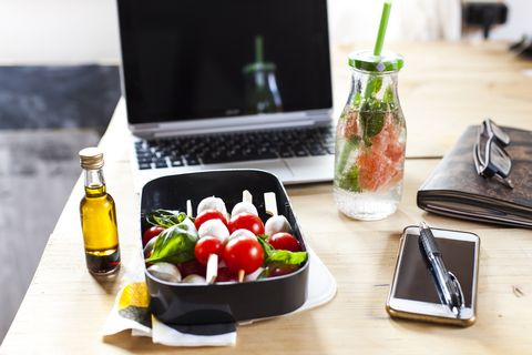 lunch box of caprese salad, bottle of infused water and laptop on desk