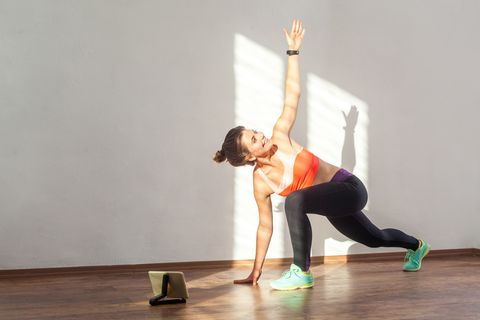 lunge with spinal twist positive fit woman with bun hairstyle and in tight sportswear practicing  indoor studio shot illuminated by sunlight from window