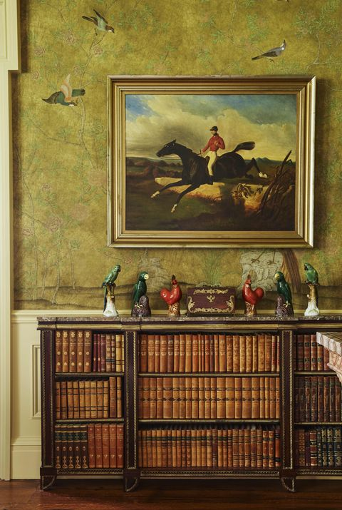 A flock of 19th-century German and Chinese ceramic birds lines a Regency rosewood bookcase in the morning room.