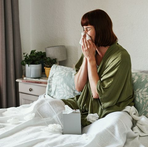 woman sneezing in bed with tissues