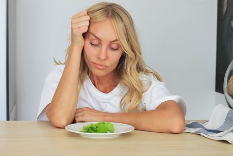 i'm fed up with untasty disgusting salad close up unhappy grimacing sad upset lady looking down at plate of lettuce on table