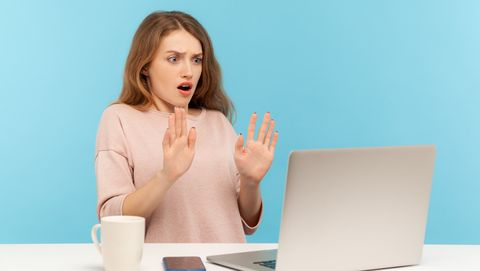 vrouw kijkt bang achter laptop
