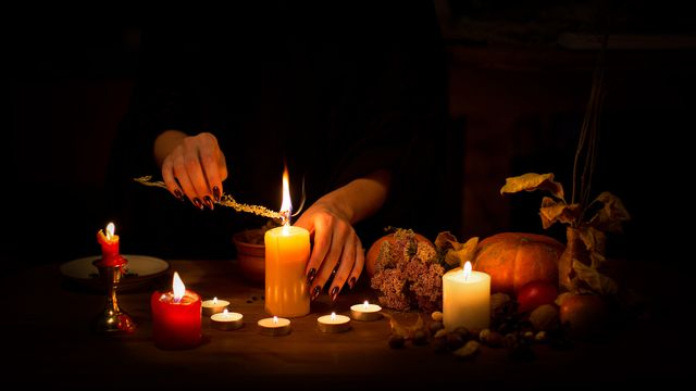 female hands with sharp black nails burning magic herb among candles, pumpkin, nuts, dry leaves