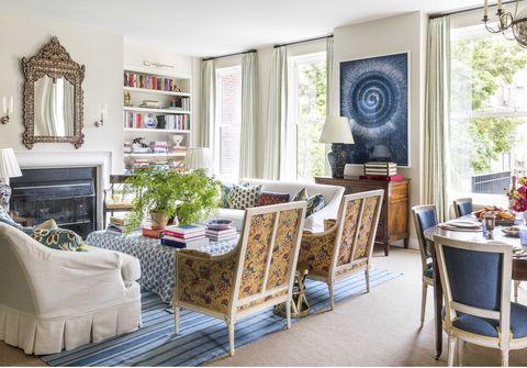 living room, indoor plants, fireplace, blue carpet, white sofa with skirt, built-in shelf