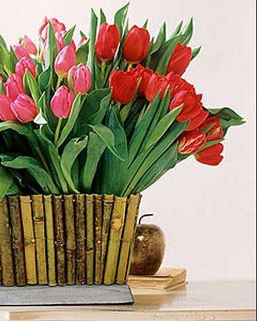 un arreglo floral con tulipanes y bambú