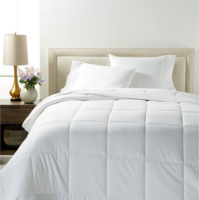 bed with white comforter, pillows, lamp, vase, brown side table