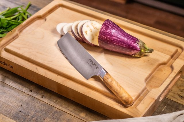 knife on cutting board next to sliced eggplant
