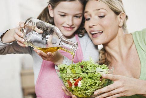una mujer y su hija aliñan una ensalada con aceite de oliva