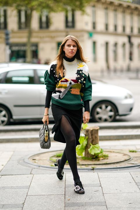 paris, france   october 06 monica de la villardiere wears a green and white wool pullover from miu miu with a printed house, a slit black skirt, a gray leather miu miu bag, tights, shoes, outside miu miu, during paris fashion week   womenswear spring summer 2021, on october 06, 2020 in paris, france photo by edward berthelotgetty images