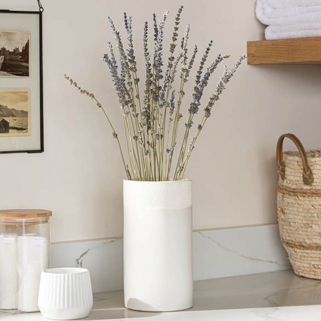 vase with lavender bunch, two magnolia candles on blue surface