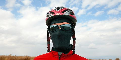 Cyclist wearing a balaclava, sunglasses, helmet, and red cycling jacket