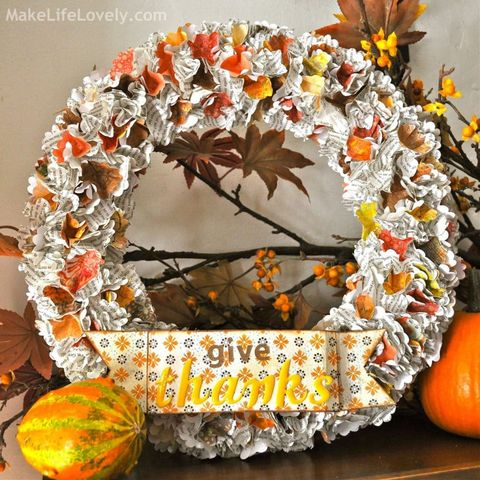 thanksgiving wreath made out of punched print paper with sign at the bottom that reads give thanks
