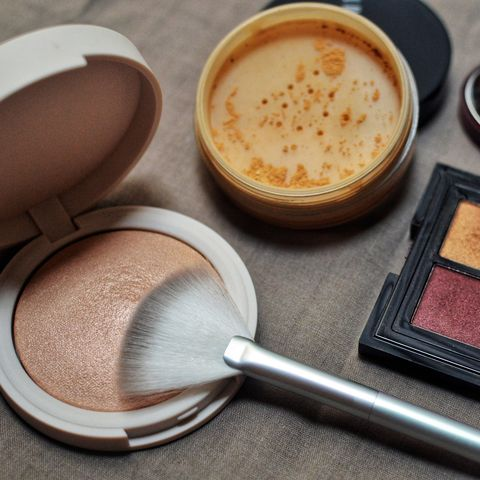 make up products   highlighter, loose powder, and eyeshadow
