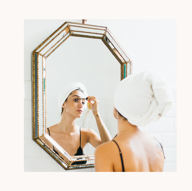 woman with a towel over her head applying mascara in the mirror