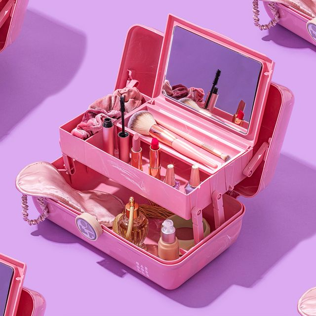 caboodles pink makeup organizers filled with makeup and brushes on purple background