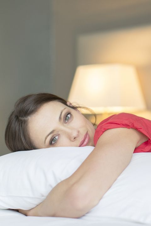 Portrait of beautiful woman wearing red dress lying on bed and hugging pillow