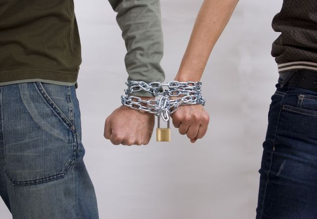 male and female hand locked in chains