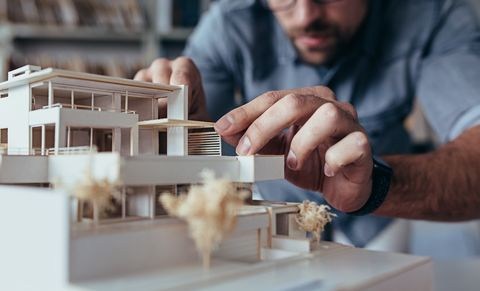 Male architect hands making model house