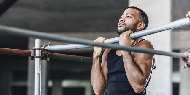 male athlete doing chin ups in a gym