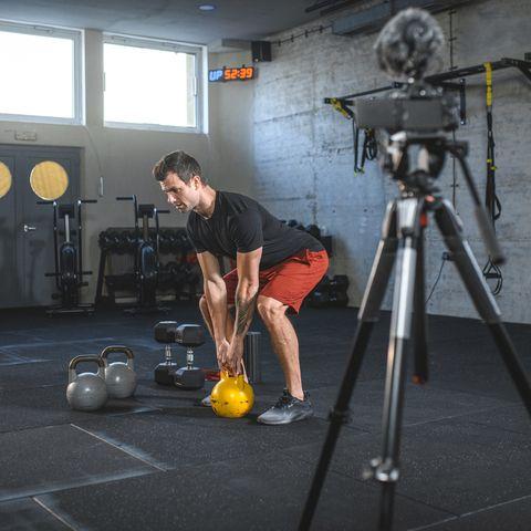Male Athlete Filming Proper Form for Kettlebell Dead Lift