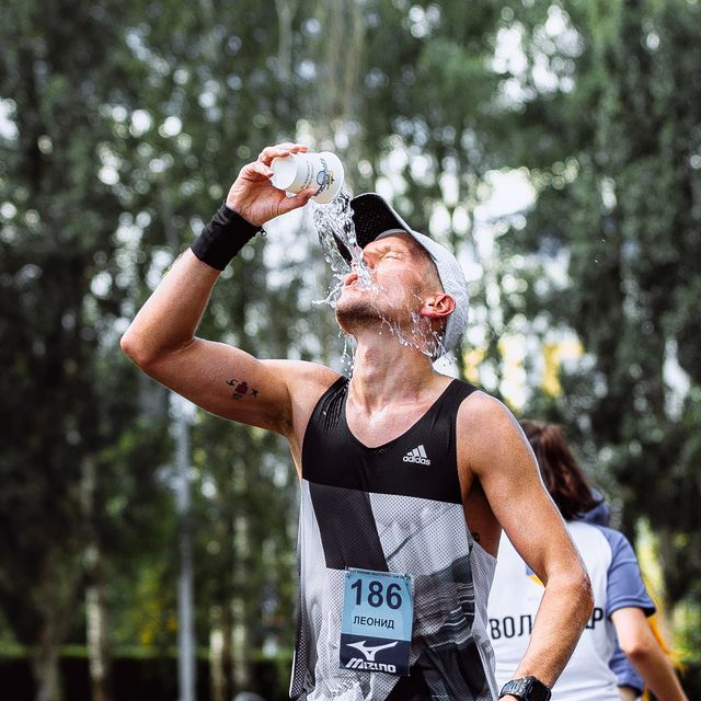 male athlete runner hot weather pouring water on head