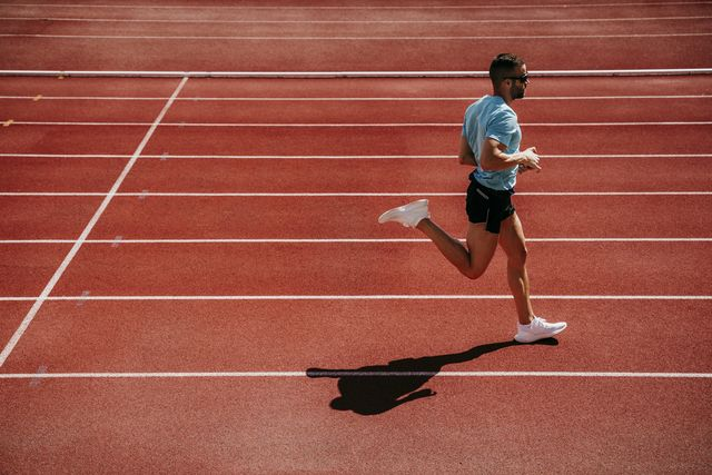 male athlete running on tartan track
