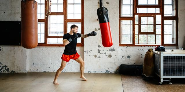 male boxer training on sandbag in a gym