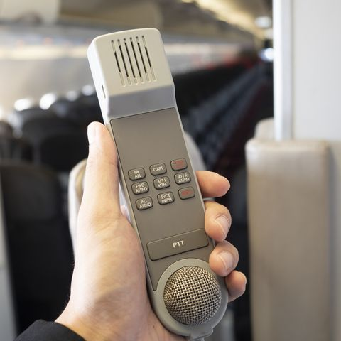 male cabin crew holding interphone in aircraft cabin