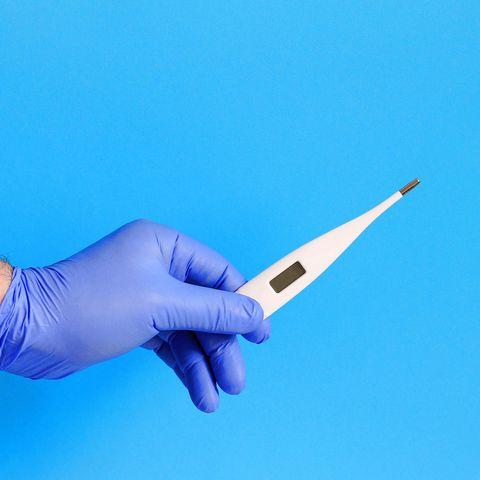 Male doctor holding digital thermometer on blue background, closeup.