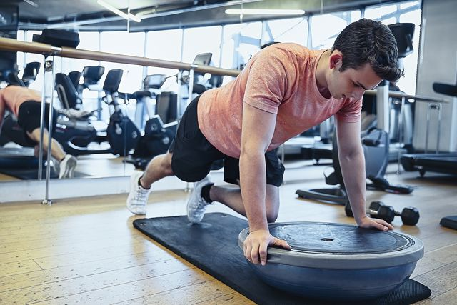 male fitness instructor working out with bosu balance ball