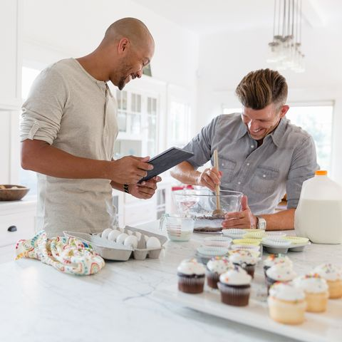 winter date ideas - Male gay couple baking cupcakes in kitchen