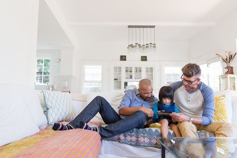Male gay parents and adopted toddler daughter using digital tablet on living room sofa