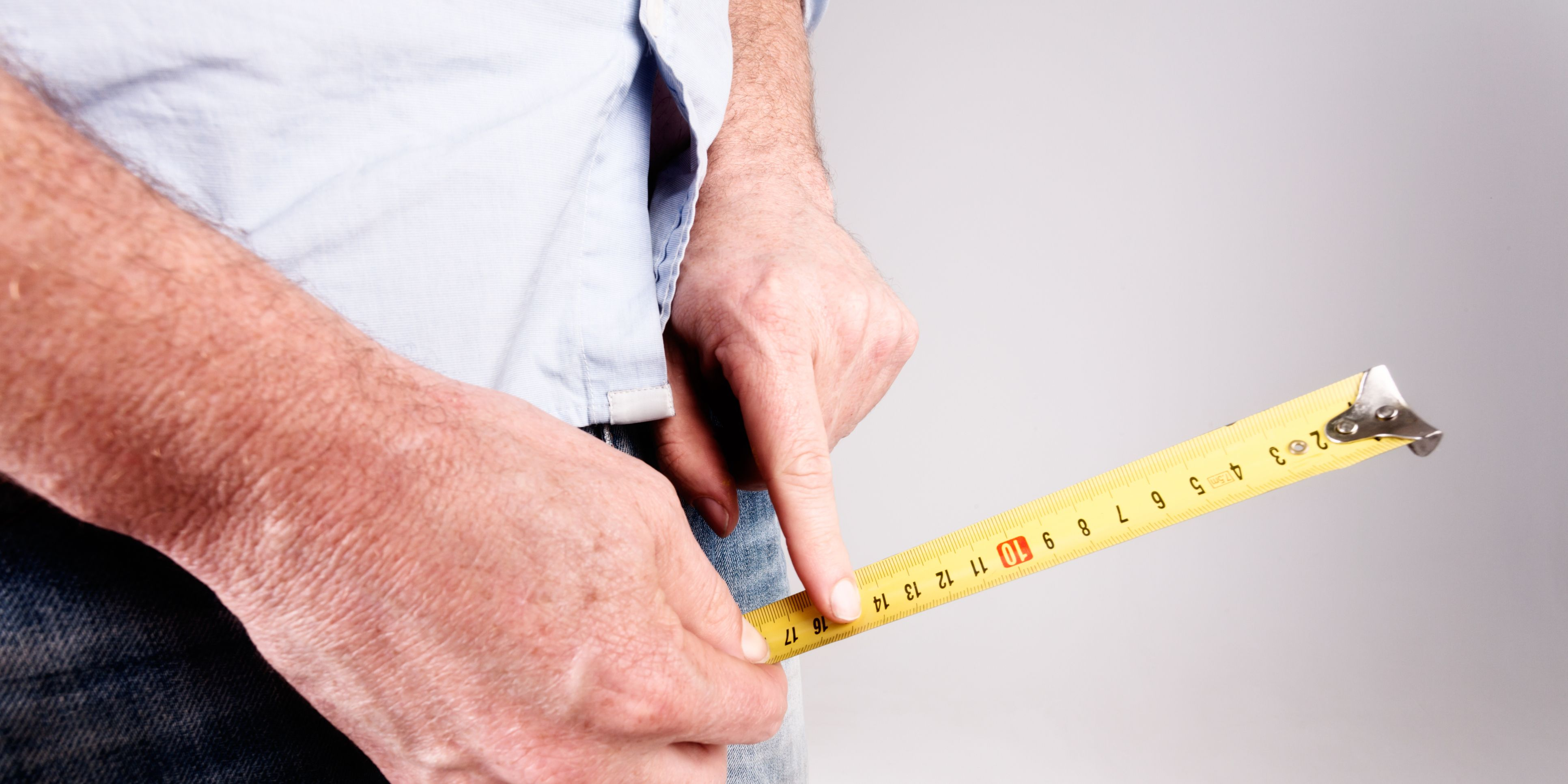 Male hands hold measuring tape to crotch