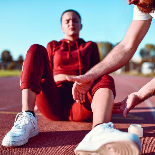Male Helping Hurt Female Athlete With Massage Cream