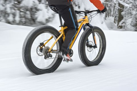 man riding a fatbike in winter on a snowy road