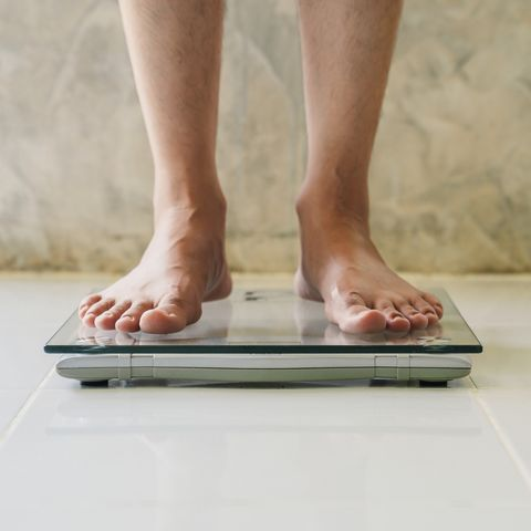 Male on weight scale on floor background, Diet concept.