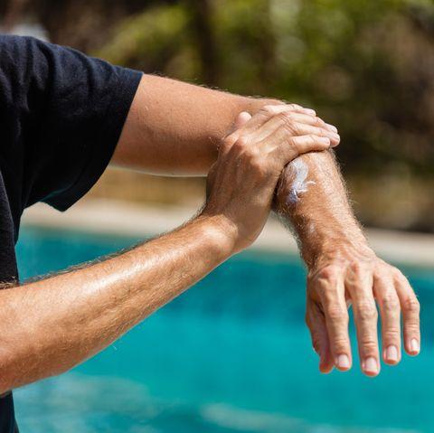 Male person using sunblock lotion