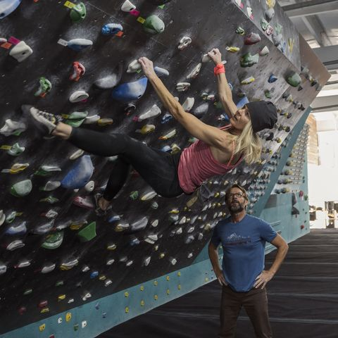 winter date ideas - Male rock climber watching female rock climber climbing wall at climbing gym
