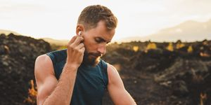 Male runner synchronizing wireless earphones with smart watch. Preparing for trail running outdoors at sunrise.