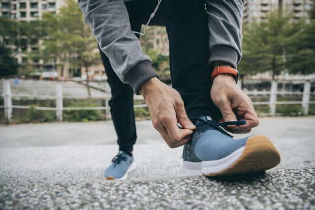 male runner tying shoe lace in a urban area