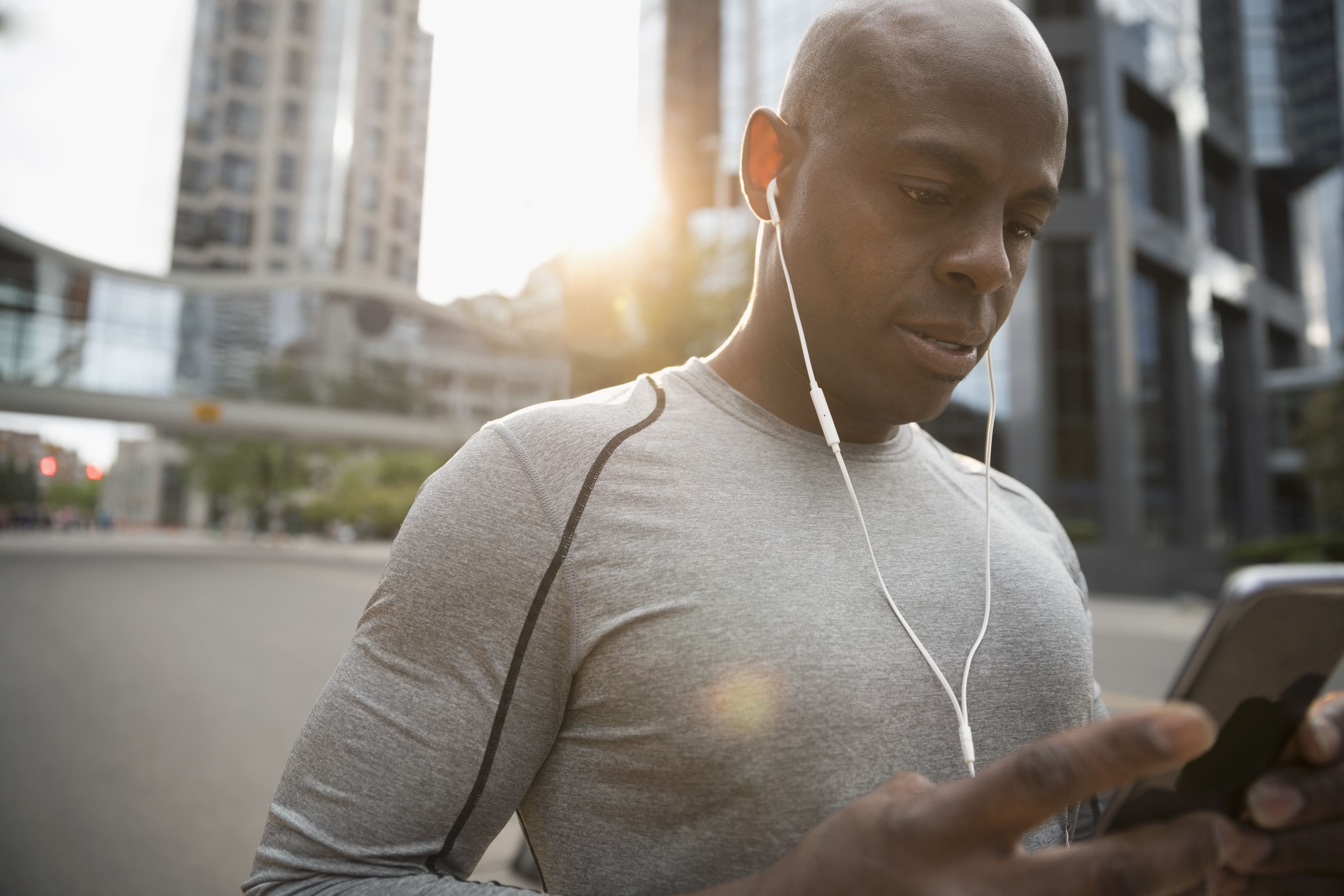 Male runner using smart phone, listening to music with earbud headphones on urban street
