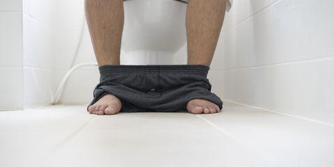 male sitting in toilet